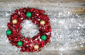 Natural Leaf Wreath With Ornaments And Snow For The Seasonal Holidays On Rustic Wood