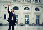 Smiling businessman waving hello to someone standing in train station