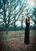 Cute Goth Girl Wearing Black Dress Stands Amongst Autumnal Trees