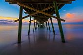 picture of inlet  - The rising sun paints the sky over the sea with vivid colors as seen from beneath the Bogue Inlet Fishing Pier - JPG