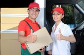 stock photo of moving van  - Smiling young man and woman postal delivery courier man before cargo van cargo delivery - JPG