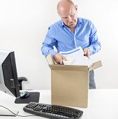 picture of last day work  - Fired and depressed man packs his belongings in a cardboard box - JPG