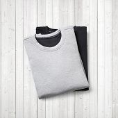 Two Jumpers On White Wood Background