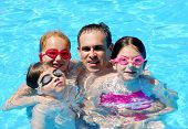 stock photo of family fun  - Family having fun in swimming pool - JPG