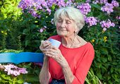 Thoughtful Old Woman With Coffee At The Garden