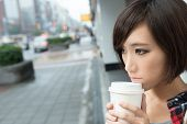Asian girl holding cup of coffee and standing and waiting on street in raining day in Taipei, Taiwan.