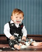 A delighted little boy totally messy as he digs into his first birthday cake.