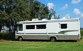image of motor coach  - RV parked in the shade of a tree - JPG