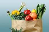 Assortment of fresh produce in grocery paper bag over gradient background