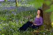 Attractive young woman among millions of bluebells wildflowers