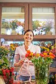 Pretty florist looking at camera while working with fresh flowers