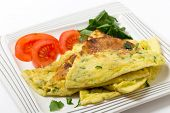 Homemade potato and parmesan cheese frittata omelet, with tomato and rocket, from an Italian recipe