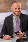 Portrait of happy smiling businessman holding mobilephone, looking at camera.