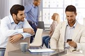 Portrait of young businessmen in office sitting by table, using mobile, talking.