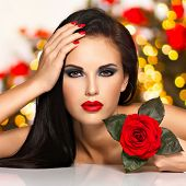Portrait of a beautiful young woman with red lips,  nails and rose flower in hand. Fashion model with black eye makeup posing at studio over night lights balls. Soft bokeh background concept.