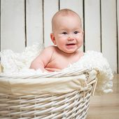 Adorable five month baby girl in wicker basket close-up