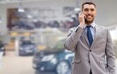 auto business, car sale, gesture and people concept - smiling businessman talking on smartphone over auto show background