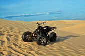 stock photo of four-wheel drive  - ATV in desert White sand dunes and blue sky - JPG