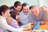 foto of health center  - group of happy people with disability having fun with tablet - JPG