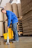 Portrait of focused man moping warehouse floor
