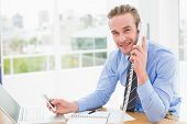 Businessman on the phone while text messaging in his office