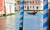 stock photo of gondolier  - A gondolier and his boat rowing through one of the many beautiful canals in Venice, Italy.