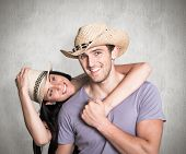 Couple in matching straw hats against weathered surface