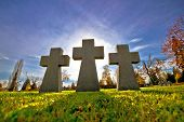 stock photo of empty tomb  - Graveyard three crosses on green meadow silhouette view - JPG