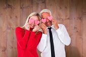 Silly couple holding hearts over their eyes against wooden planks