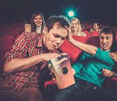 Impudent young man steals popcorn in cinema while people watching movie