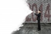 Businessman Spray White Cloud Covering Old 2014 Dark Brick Wall