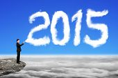 Businessman Spraying 2015 Year Cloud Shape In Blue Sky Cloudscape