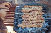 Raw meat is fried at the stake. Male fry the kebabs on the grill.