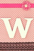 Wooden letter W on polka dots background