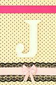 Wooden letter J on polka dots background