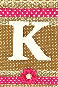 Wooden letter K on polka dots background