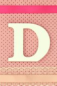 Wooden letter D on polka dots background