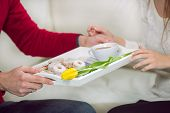 The boy brings his girlfriend on a tray coffee and cookies. Selective focus