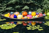 stock photo of lilly  - Colorful glass balls in a garden lake coverend in lilly pads - JPG