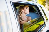 picture of limousine  - Bride looks out of the window a white limousine - JPG