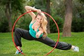 Young female athlete with hula hoop in the park