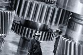 two industry workers and giant cogwheels machinery, engineering and technology