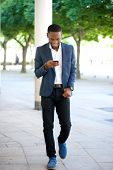 Handsome Man Walking And Sending Text Message On Cellphone