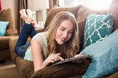 Young woman looking at her tablet on the couch