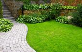 Garden stone path with grass growing up between the stones poster