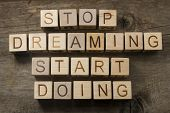 Stop dreaming. Start doing. Motivational text on a wooden background