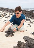 stock photo of ten years old  - building a cairn  - JPG