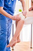 picture of knee  - Doctor is rewinding knee bandage to young woman - JPG