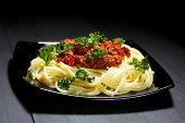 Spaghetti bolognese in black plate on dark background
