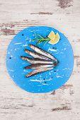 Fresh Sardines On Blue Kitchen Board.